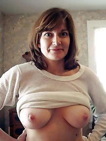 Erotic older mistress is showing off her tits